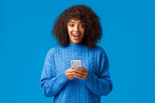 Eccitato e sopraffatto sorridente attraente giovane donna afro-americana, che indossa un maglione blu invernale, guardando la fotocamera stupita e sorpresa come ricevere grandi notizie sul messaggio dello smartphone