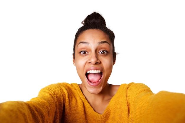 Eccitato giovane donna africana prendendo selfie e ridendo