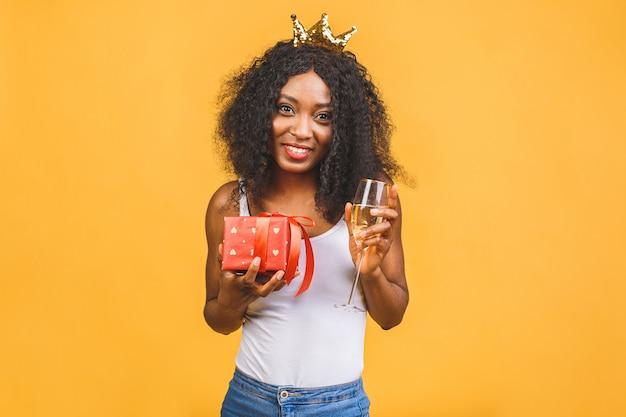 Eccitato giovane donna nera afroamericana che tiene presente casella e bicchiere di champagne