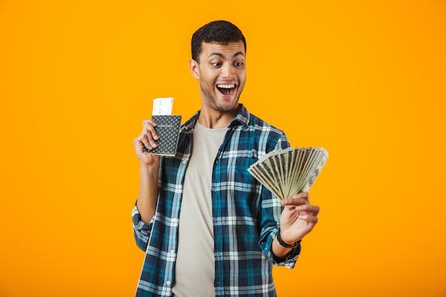 Eccitato giovane uomo che indossa la camicia a quadri in piedi isolato su sfondo arancione, mostrando banconote di denaro, tenendo il passaporto con i biglietti aerei