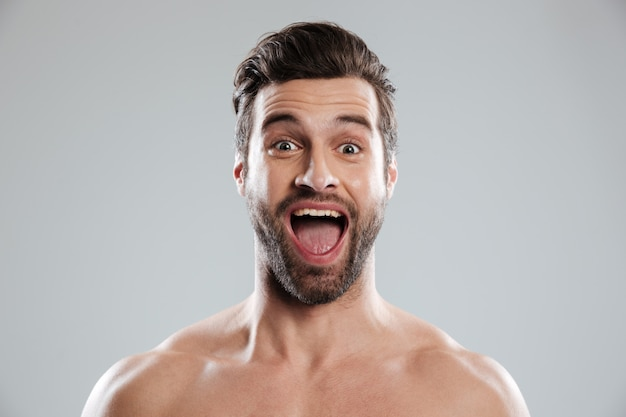 Eccitato uomo barbuto con spalle nude e bocca aperta