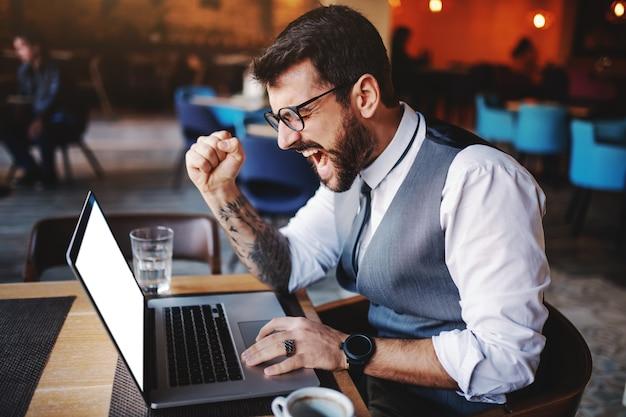 Eccitato uomo d'affari caucasico barbuto in tuta e con occhiali tifo per un eccellente lavoro fatto. una mano è sul laptop mentre con l'altro uomo che mostra un pugno.