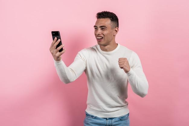 Eccitato uomo felice mulatta in possesso di uno smartphone in mano e guardando lo schermo