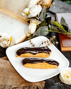 Eclairs di cioccolato zuccherato su un piatto