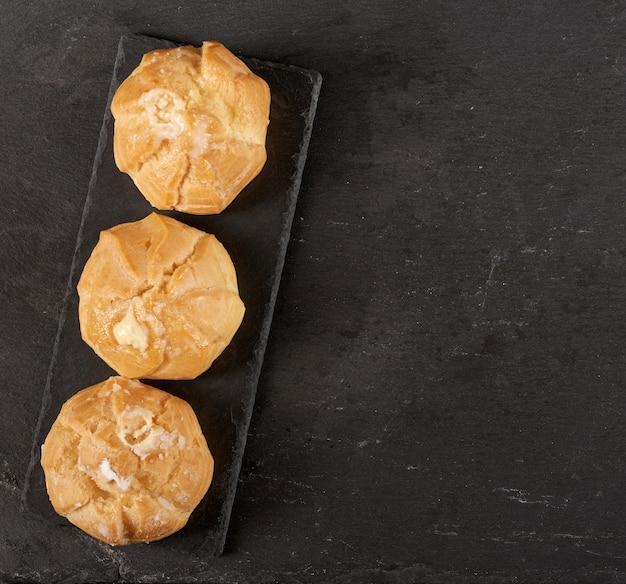 Eclairs di crema pasticcera al forno su un bordo nero