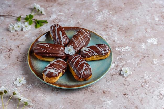 Eclairs o profiteroles con cioccolato nero e cioccolato bianco con crema pasticcera dentro, dessert francese tradizionale vista dall'alto.