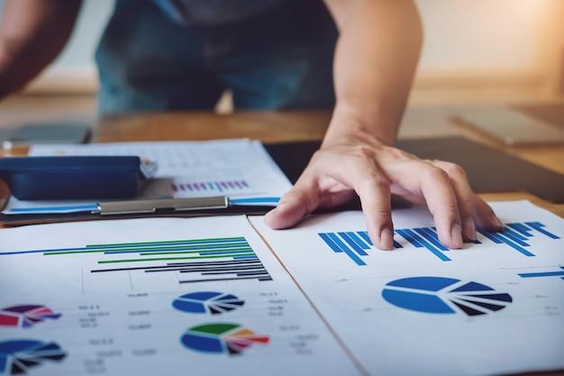 Economista che analizza l'ordine di compera del documento del grafico di vendita di riserva nelle azione del mercato.