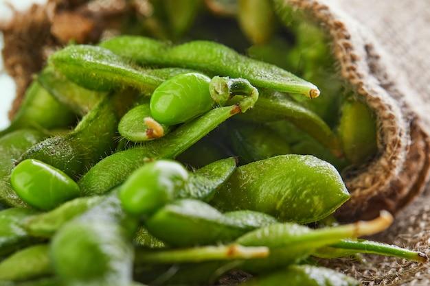 Edamame o semi di soia si rovesciano fuori dalla borsa su un sacco marrone