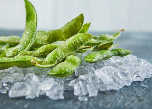 Edamame o soia congelati nella miscela con ghiaccio tritato su un fondo blu