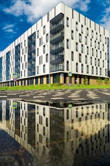 Edifici di colore bianco creati in uno stile contemporaneo. l'erba e gli alberi inferiori. l'edificio ospita l'università innopolis della città, kazan