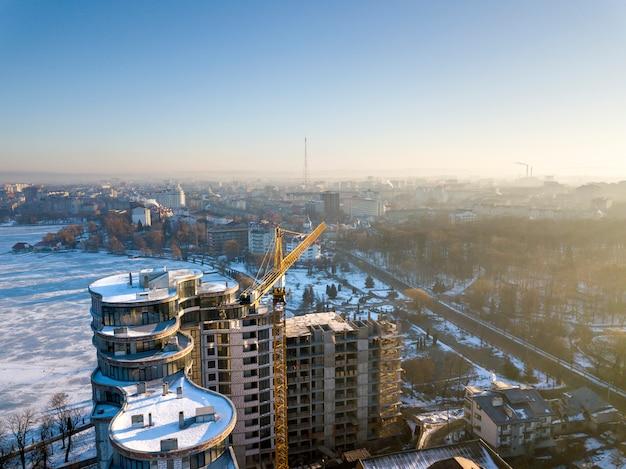 Edificio alto dell'ufficio o dell'appartamento in costruzione, vista aerea. siluetta della gru a torre campo di snowy e città distante sul fondo luminoso dello spazio della copia del cielo blu. fotografia di droni.