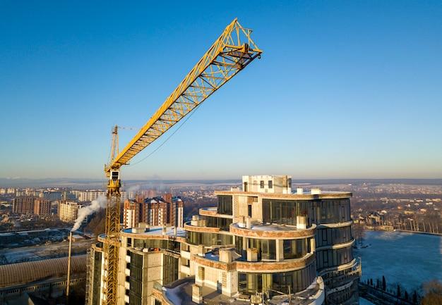 Edificio alto dell'ufficio o dell'appartamento in costruzione, vista superiore. gru a torre sul fondo luminoso dello spazio della copia del cielo blu, paesaggio della città che allunga all'orizzonte. drone fotografia aerea.