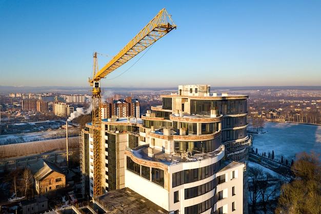 Edificio alto dell'ufficio o dell'appartamento in costruzione, vista superiore. gru a torre sullo spazio luminoso della copia del cielo blu, paesaggio della città che allunga all'orizzonte. drone fotografia aerea.