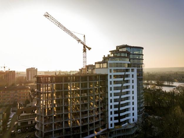 Edificio alto dell'ufficio o dell'appartamento in costruzione, vista superiore. la gru a torre e la città abbelliscono l'allungamento all'orizzonte. drone fotografia aerea.