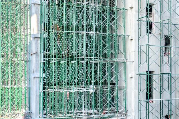 Edificio alto in costruzione con impalcature verdi.