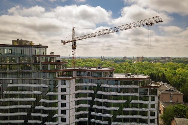 Edificio alto incompiuto per uffici o appartamenti in costruzione tra le cime degli alberi verdi. gru a torre sullo spazio luminoso della copia del cielo blu.