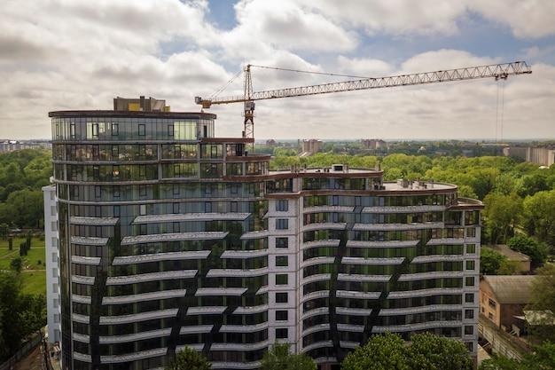 Edificio alto incompiuto per uffici o appartamenti in costruzione tra le cime degli alberi verdi.