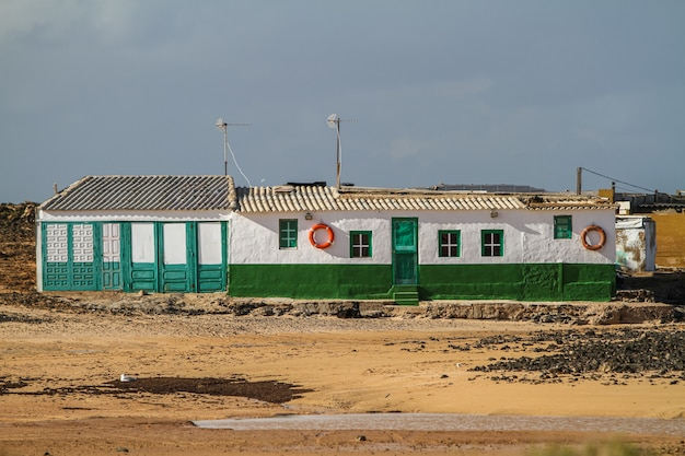 Edificio bianco e verde nel mezzo di un campo a fuerteventura
