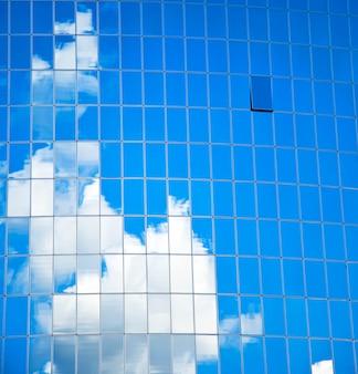 Edificio di vetro highrise con riflessione di cielo e nuvole
