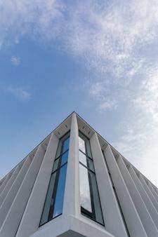 Edificio moderno con pareti esterne in vetro e cielo.