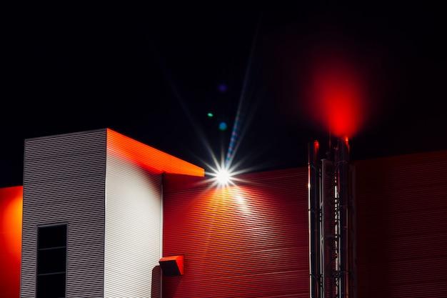 Edificio per uffici rosso con fumo dal tubo nella notte. architettura moderna con copia spazio sul cielo scuro con riflesso lente. struttura industriale da vicino. vista in basso sul grande muro rosso. brilla nuvola sopra il tetto.