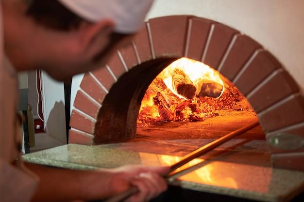 Ef prepara la pizza nel tradizionale forno di mattoni.