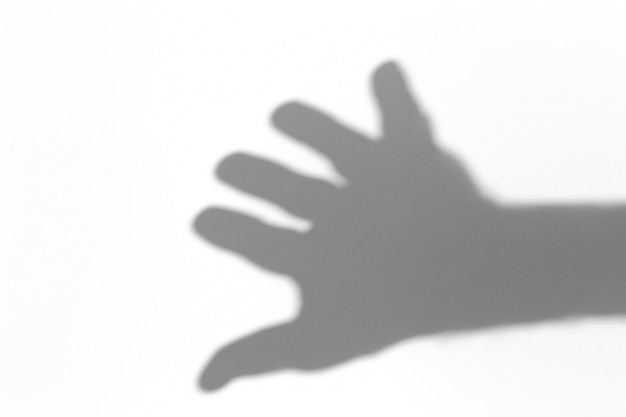 Effetto di sovrapposizione delle ombre. ombre dai palmi delle mani sul muro di luce bianca alla luce del sole.