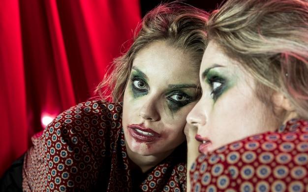 Effetto specchio multiplo di donna che guarda l'obbiettivo dallo specchio