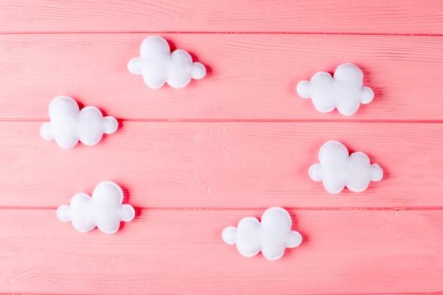 Elabora nuvole bianche con cornice, copyspace su fondo in legno rosa. giocattoli di feltro fatti a mano.