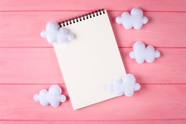 Elabora nuvole bianche con il taccuino, copyspace su fondo di legno rosa. giocattoli di feltro fatti a mano