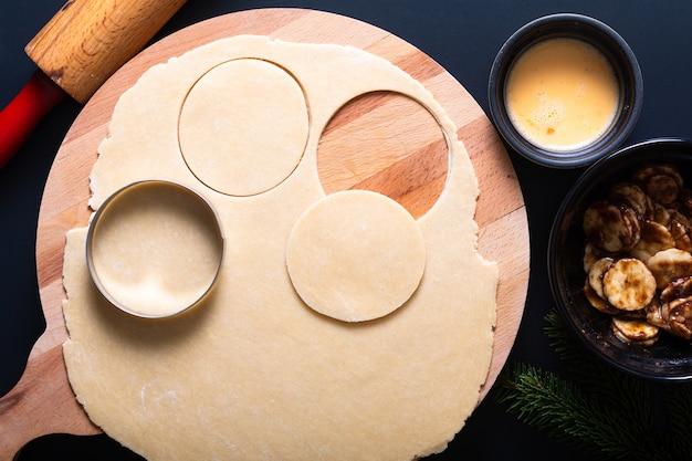 Elaborazione di concetto dell'alimento per produrre la torta casalinga adottiva della mano della banana sul nero
