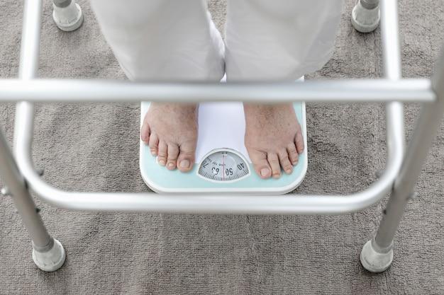 Eldely femmina in piedi su una bilancia, il suo peso misura 54 kg.