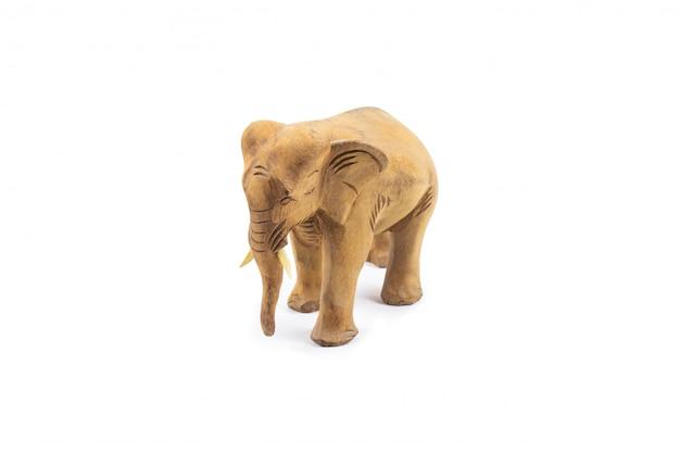 Elefante scolpito in legno duro isolato su un muro bianco.