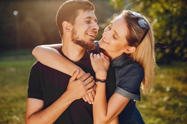 Elegante amorevole coppia in piedi in un parco.