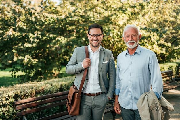 Elegante anziano e giovane che cammina nel parco.