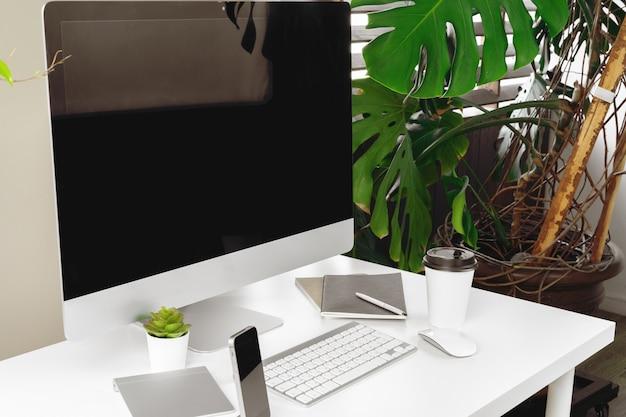 Elegante area di lavoro con computer, tastiera, articoli per ufficio e pianta in ufficio moderno
