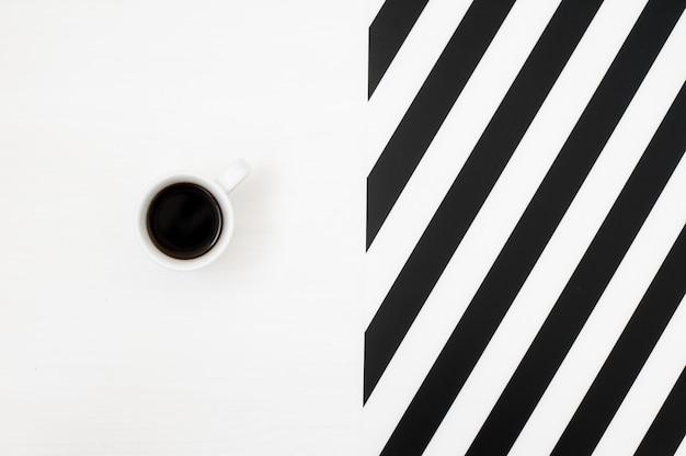 Elegante area di lavoro minimalista con una tazza di caffè su sfondo a righe