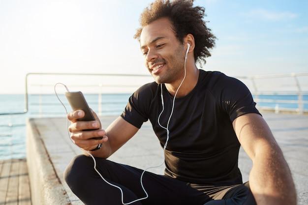Elegante atleta maschio dalla carnagione scura con acconciatura afro utilizzando il telefono cellulare, sorridente, scegliendo la canzone migliore per l'allenamento