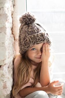 Elegante bambina che copre la metà del viso