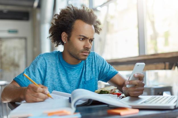 Elegante bel ragazzo con la pelle scura seduto alla mensa che scrive qualcosa nel suo libro di testo che tiene il cellulare che sfoglia le notizie tramite i social network online cercando perplesso di scoprire cattive notizie