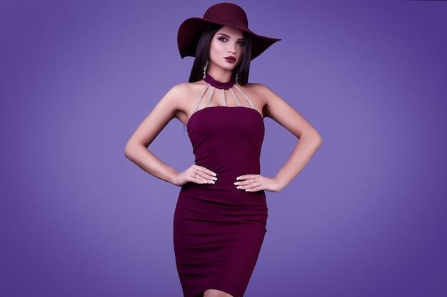 Elegante bella donna bruna in un vestito viola e cappello largo