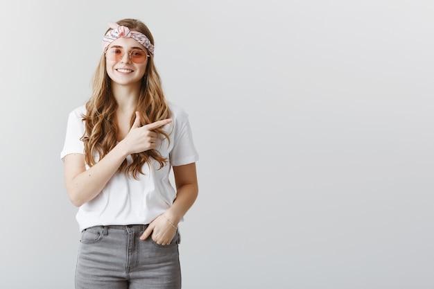Elegante bella ragazza bionda in occhiali da sole che punta il dito a destra