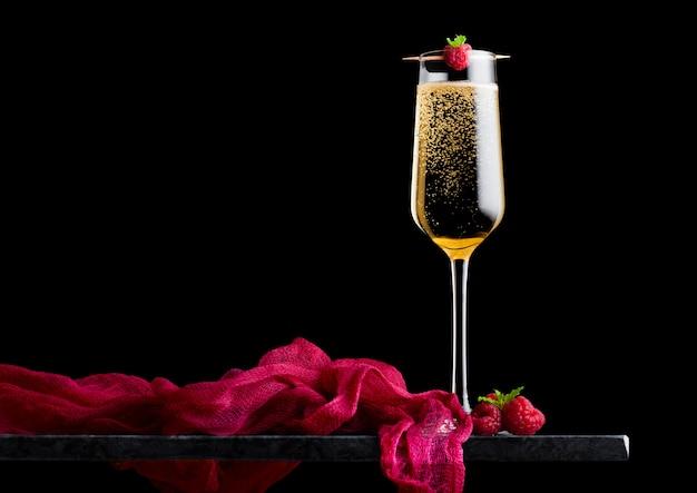 Elegante bicchiere di champagne giallo con rasspbery e bacche fresche con foglia di menta sul bastone sul bordo di marmo nero sul nero.
