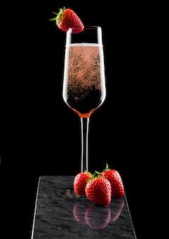 Elegante bicchiere di rose rosa champagne con fragole in cima e bacche fresche sul bordo di marmo nero su fondo nero.