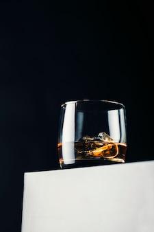 Elegante bicchiere di whisky con cubetti di ghiaccio su un supporto bianco