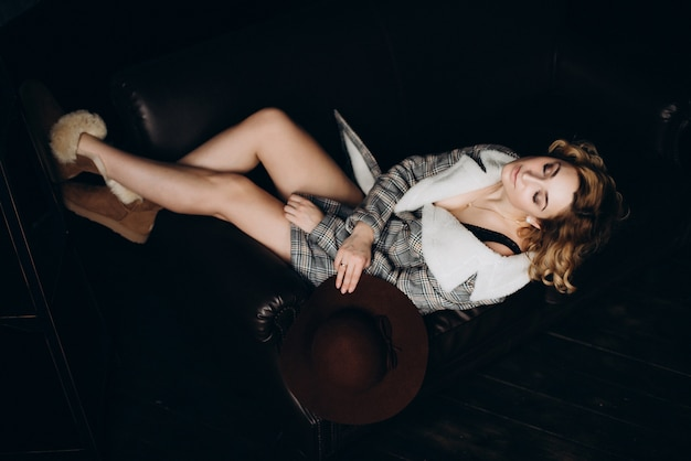 Elegante bionda con gli stivali e un cappotto sul suo corpo nudo su un divano in pelle nera in una stanza in stile loft.