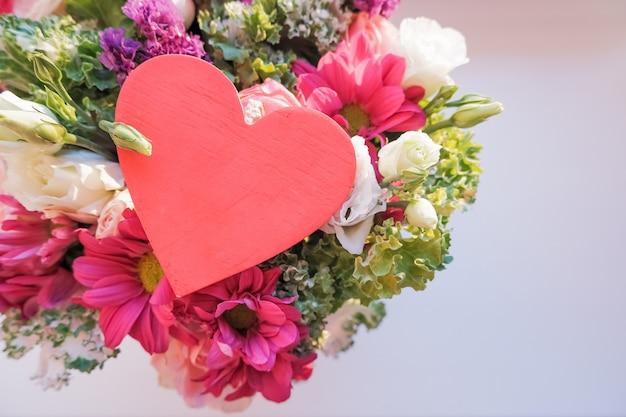 Elegante bouquet di san valentino con fiori di rose, lisianthus, crisantemo e cuore in legno rosso, segno d'amore. buon san valentino.