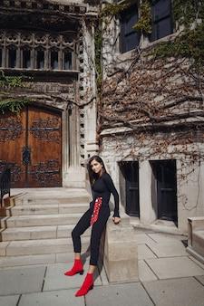 Elegante bruna in piedi accanto al entance di un edificio