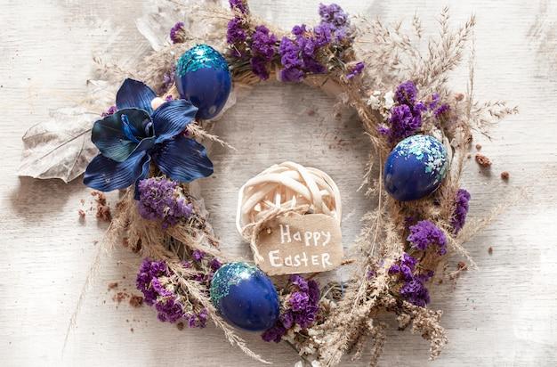 Elegante composizione con ghirlanda pasquale e uova di tendenza blu.