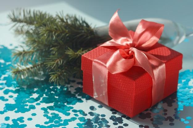 Elegante composizione festiva con confezione regalo rossa con fiocco in corallo satinato, rami di albero di natale e coriandoli blu cosparsi.